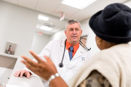 Male Doctor talking with elderly female patient outside exam room.